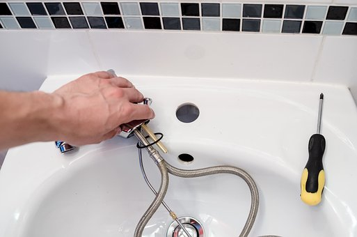Commercial plumber fixing the sink